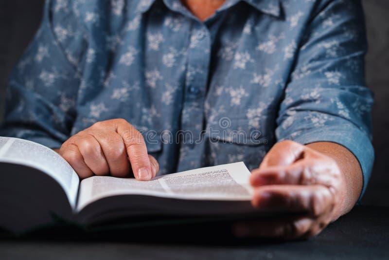 Mujer mayor que lee el libro grueso en casa Abuela con la biblia Pensionista mayor concentrado con las arrugas en las manos imágenes de archivo libres de regalías