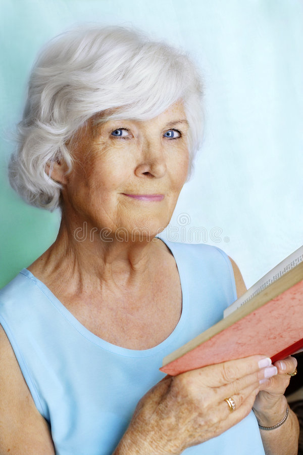 Mujer mayor que lee un libro fotos de archivo libres de regalías