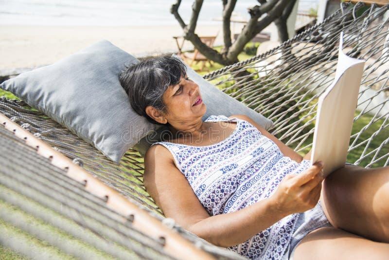 Mujer mayor que lee una revista en una hamaca foto de archivo