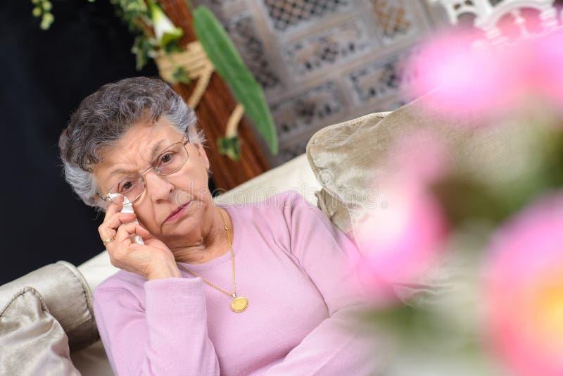 Mujer mayor que limpia los rasgones imagen de archivo