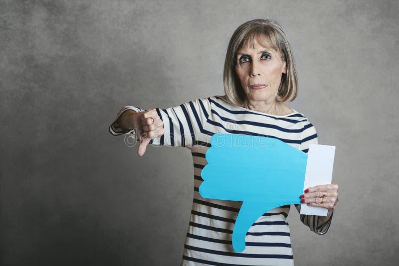 Mujer mayor que lleva a cabo un icono de la aversión imagenes de archivo