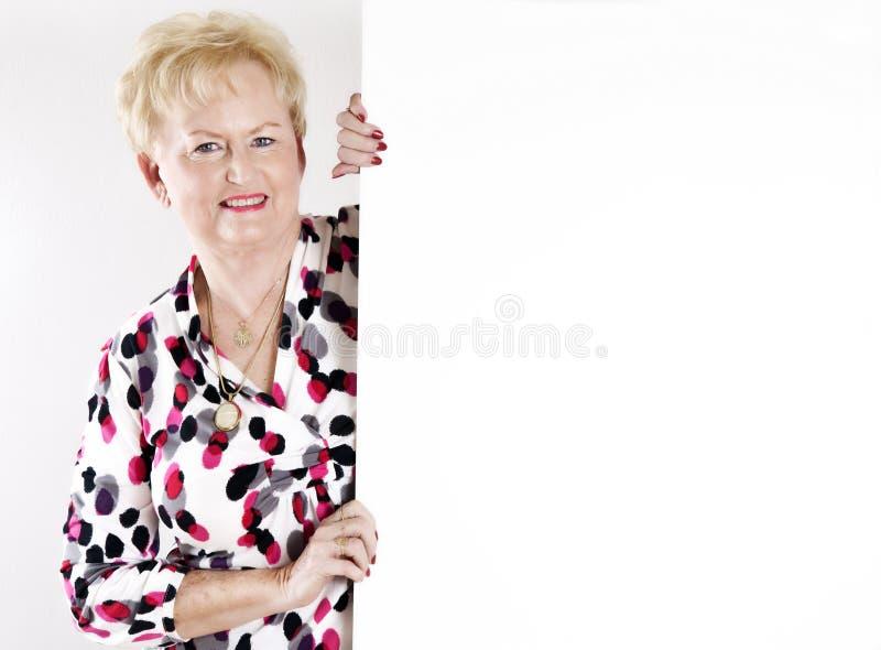 Mujer mayor que lleva a cabo una muestra blanca en blanco imagenes de archivo
