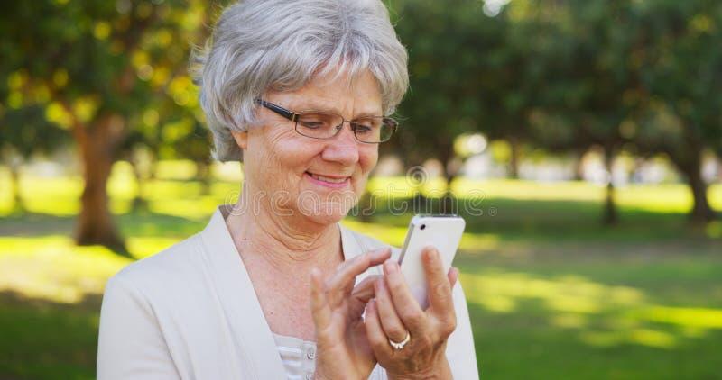 Mujer mayor que manda un SMS en smartphone al aire libre foto de archivo