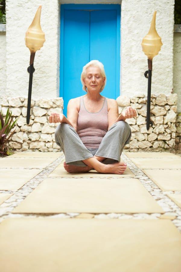 Mujer mayor que medita al aire libre en el balneario de la salud fotos de archivo libres de regalías