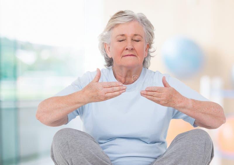 Mujer mayor que medita contra fondo brillante imagen de archivo