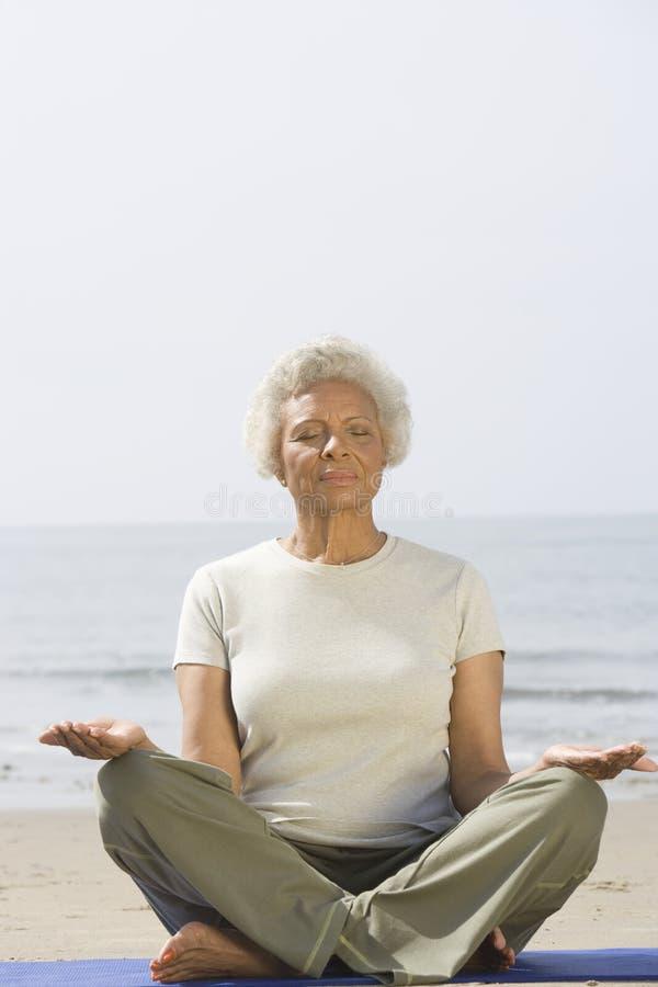 Mujer mayor que medita en la playa foto de archivo libre de regalías