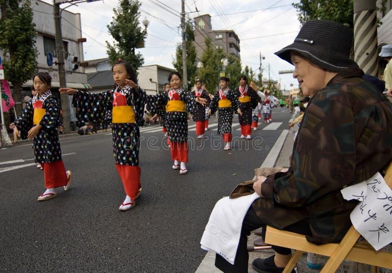 Mujer mayor que mira a bailarines japoneses del festival foto de archivo