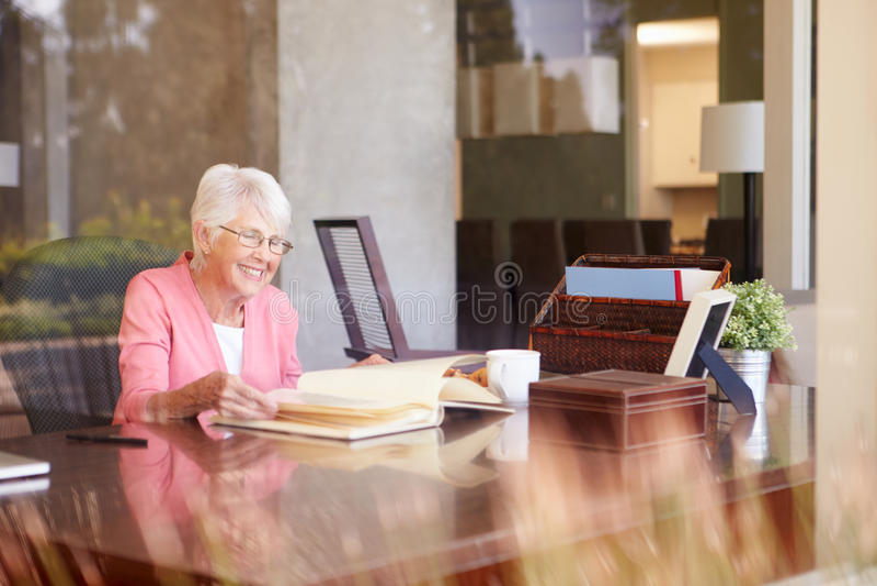 Mujer mayor que mira el álbum de foto a través de ventana fotografía de archivo