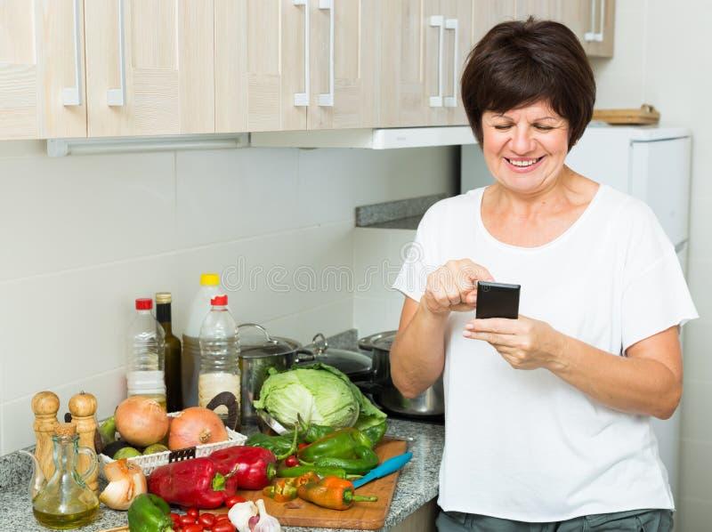 Mujer mayor que mira el teléfono imagen de archivo libre de regalías