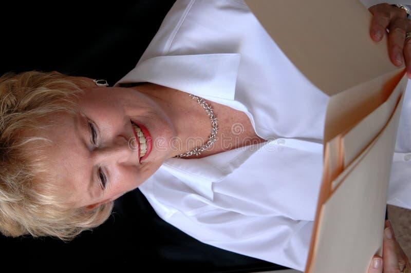 Mujer mayor que mira ficheros imagenes de archivo