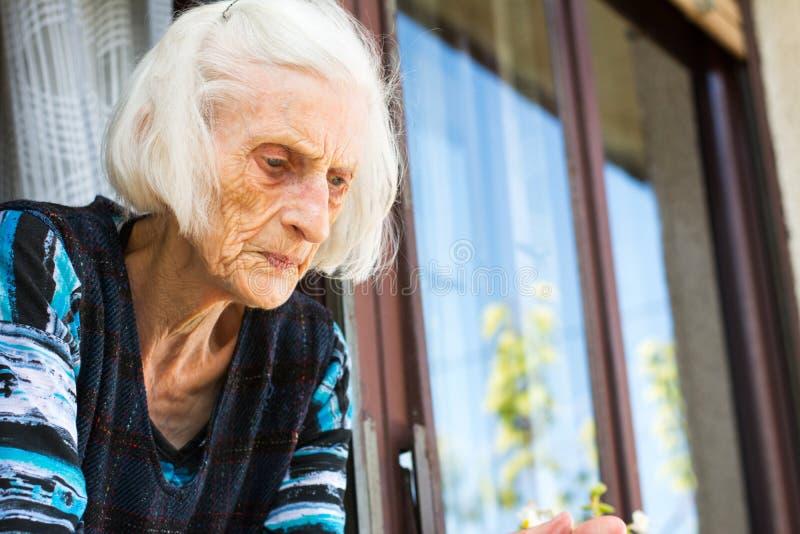 Mujer mayor que mira fuera de la ventana casera imagen de archivo