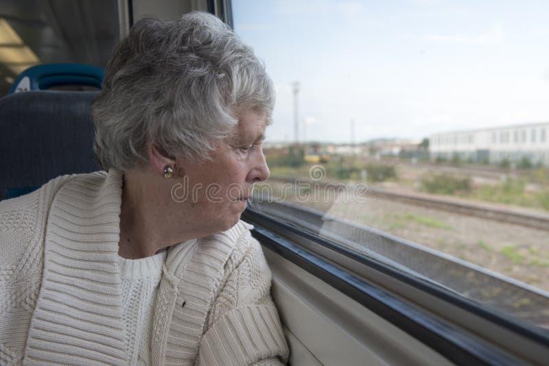 Mujer mayor que mira fuera de la ventana en un tren fotografía de archivo