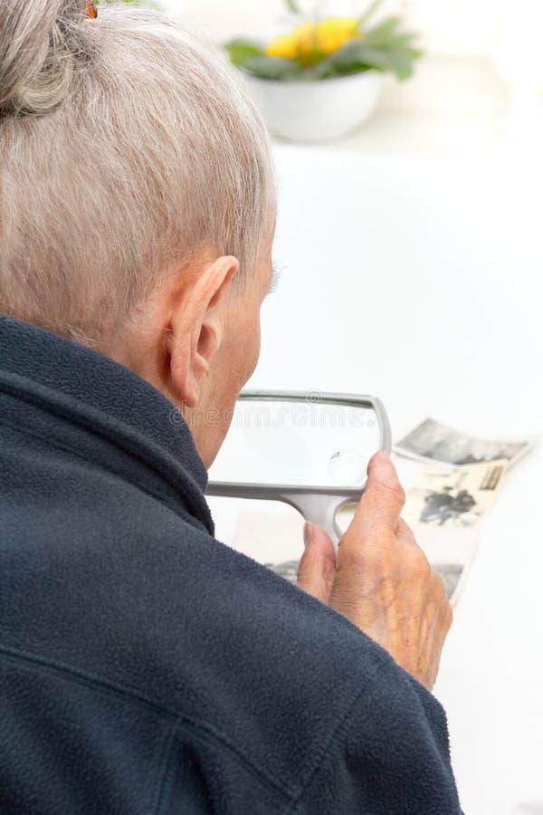 Mujer mayor que mira la lupa de las fotos foto de archivo libre de regalías