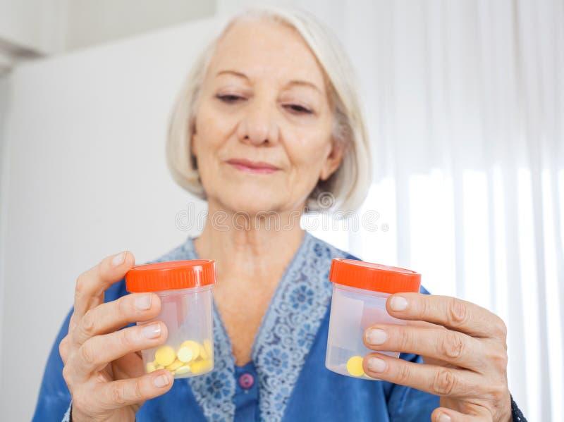 Mujer mayor que mira las botellas de píldora fotografía de archivo libre de regalías