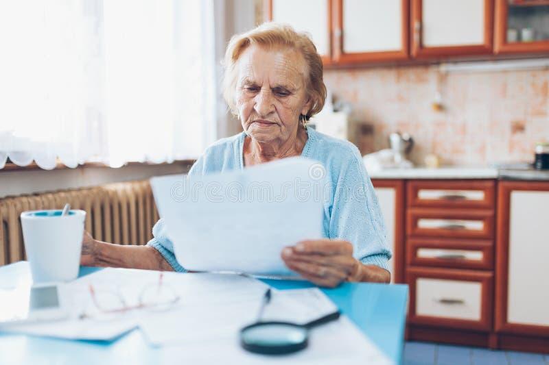 Mujer mayor que mira sus facturas de servicios públicos foto de archivo