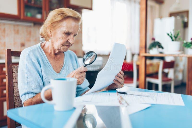 Mujer mayor que mira sus facturas de servicios públicos imagen de archivo libre de regalías
