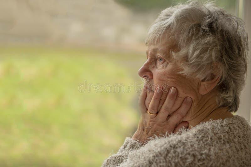 Mujer mayor que mira trastorno a través de una ventana fotografía de archivo libre de regalías