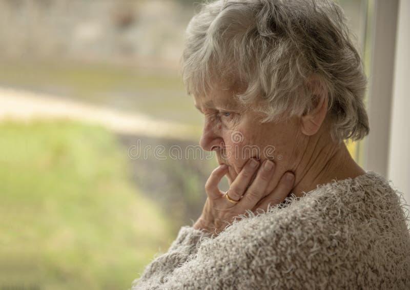 Mujer mayor que mira trastorno a través de una ventana imagen de archivo