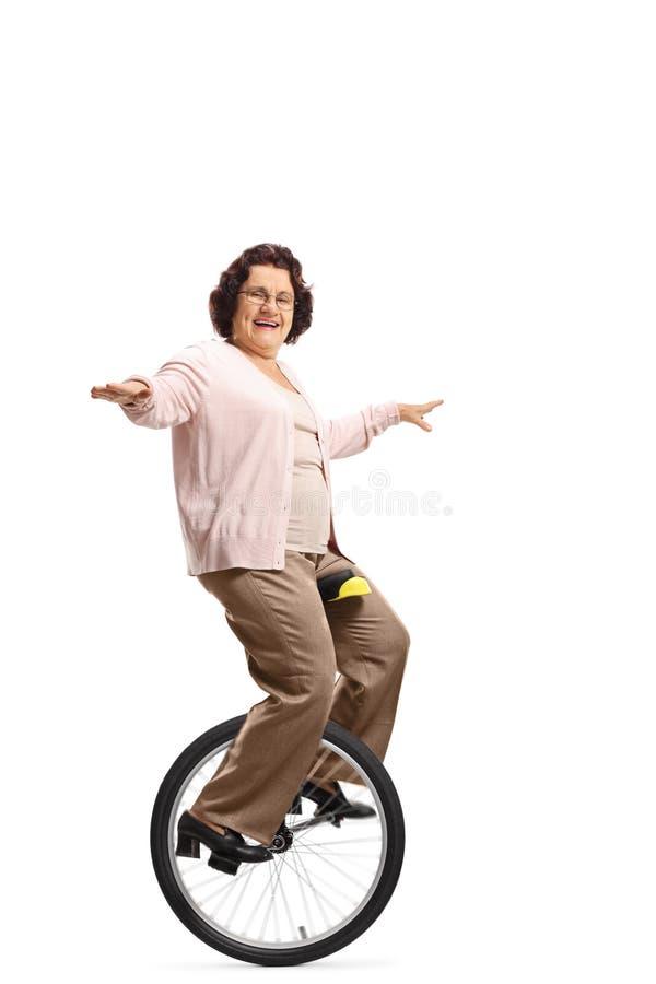 Mujer mayor que monta un unicycle y una sonrisa imagen de archivo libre de regalías