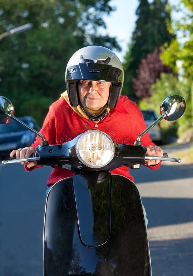 Mujer mayor que monta una vespa foto de archivo libre de regalías