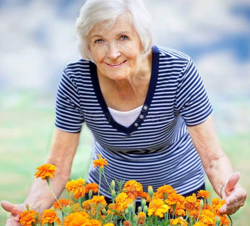 Mujer mayor que muestra las flores fotos de archivo