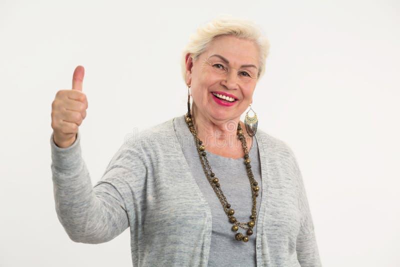 Mujer mayor que muestra los pulgares para arriba fotos de archivo