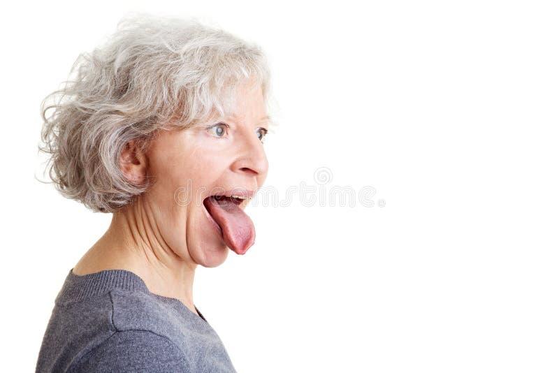 Mujer mayor que muestra su lengüeta fotografía de archivo libre de regalías