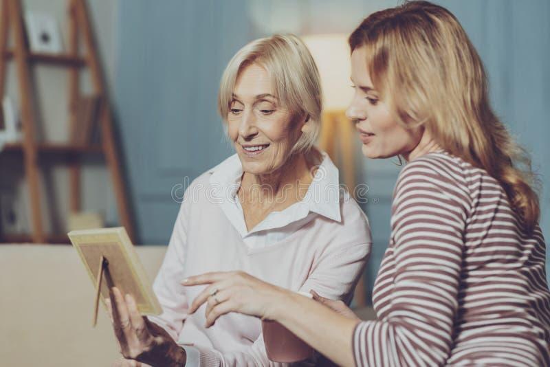 Mujer mayor que muestra una foto a su hija imagen de archivo