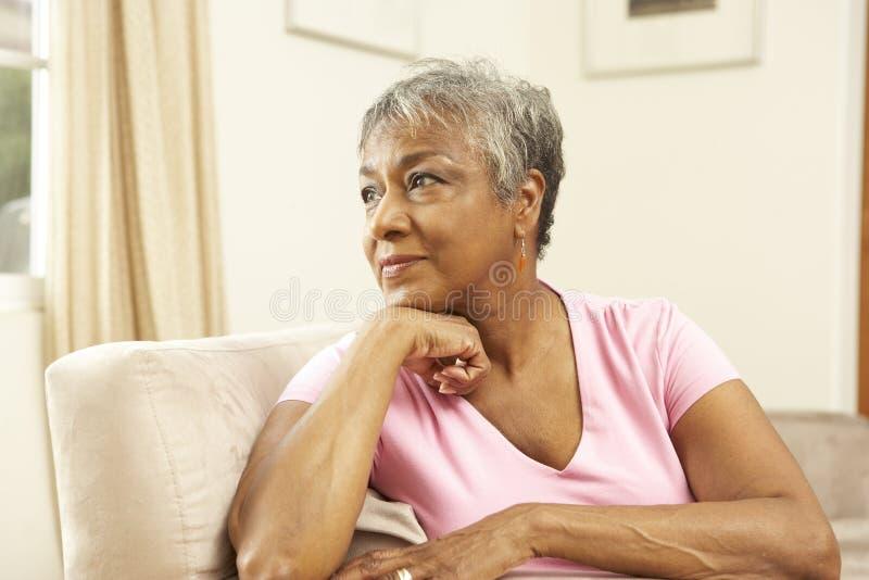 Mujer mayor que parece pensativa en silla fotos de archivo libres de regalías