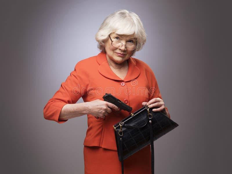 Mujer mayor que pone el arma en bolso fotografía de archivo libre de regalías