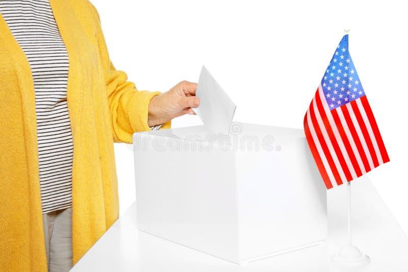 Mujer mayor que pone la papeleta electoral en la caja contra el fondo blanco foto de archivo libre de regalías