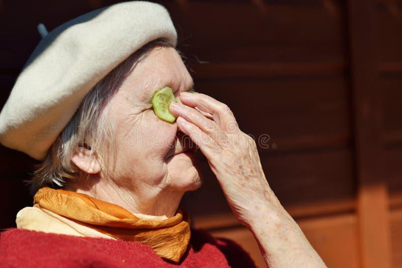 Mujer mayor que pone los pepinos en sus ojos fotos de archivo