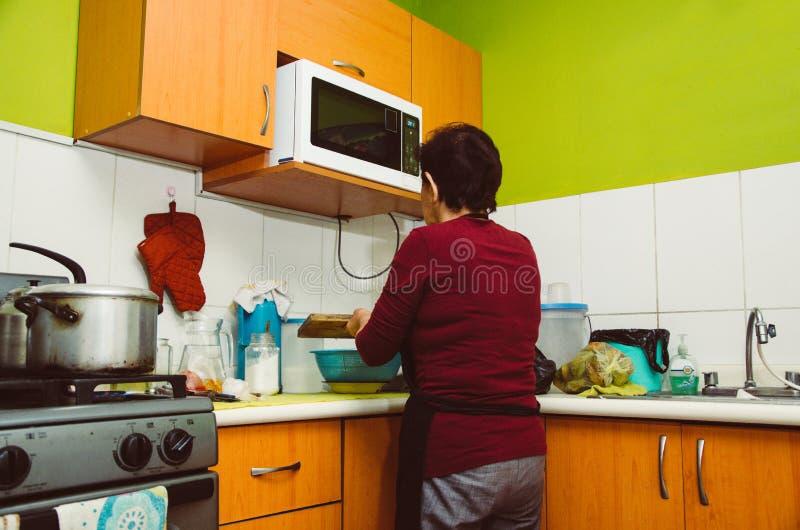 Mujer mayor que prepara la comida sana de verduras frescas imagenes de archivo