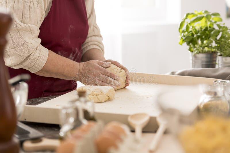 Mujer mayor que prepara las pastas frescas imagen de archivo