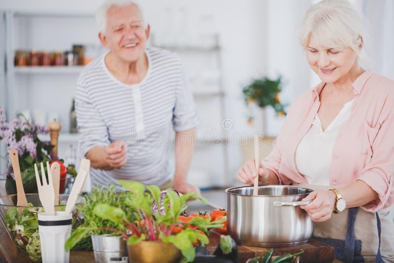 Mujer mayor que prepara una comida imagenes de archivo