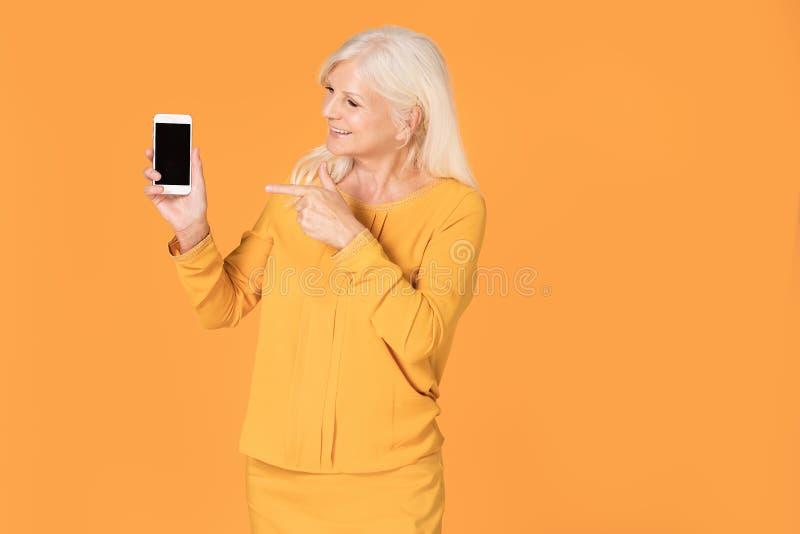 Mujer mayor que presenta con el teléfono móvil imagen de archivo