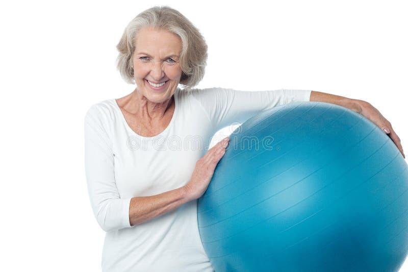 Mujer mayor que presenta con la bola del ejercicio imagen de archivo libre de regalías