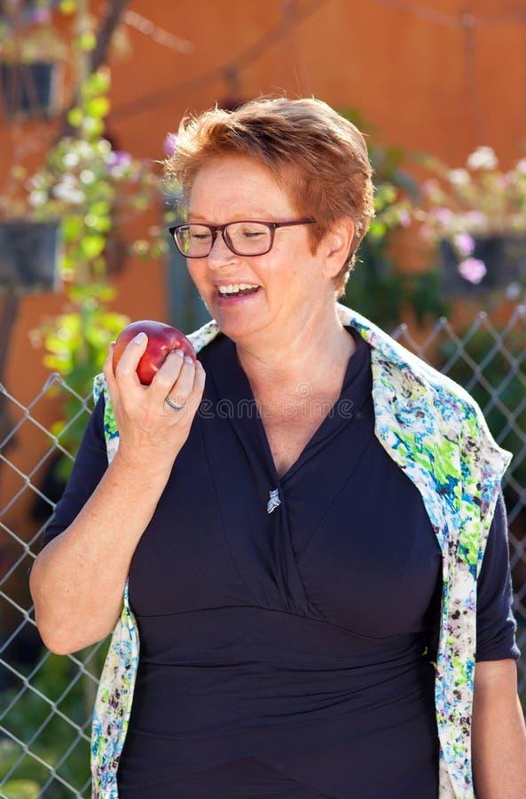 Mujer mayor que ríe como ella sostiene una manzana roja fotografía de archivo