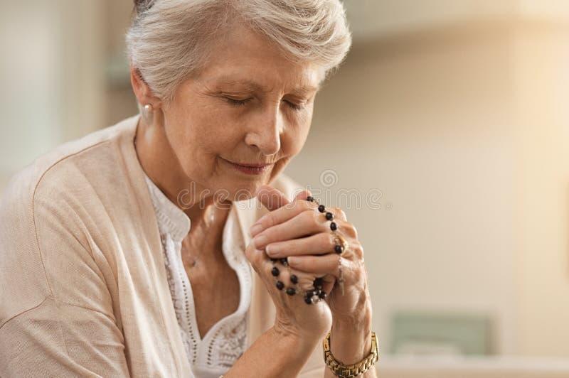 Mujer mayor que ruega fotografía de archivo