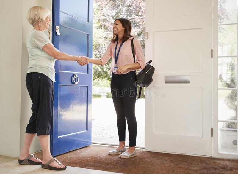 Mujer mayor que saluda al trabajador de sexo femenino del cuidado que hace a casa visita fotografía de archivo libre de regalías