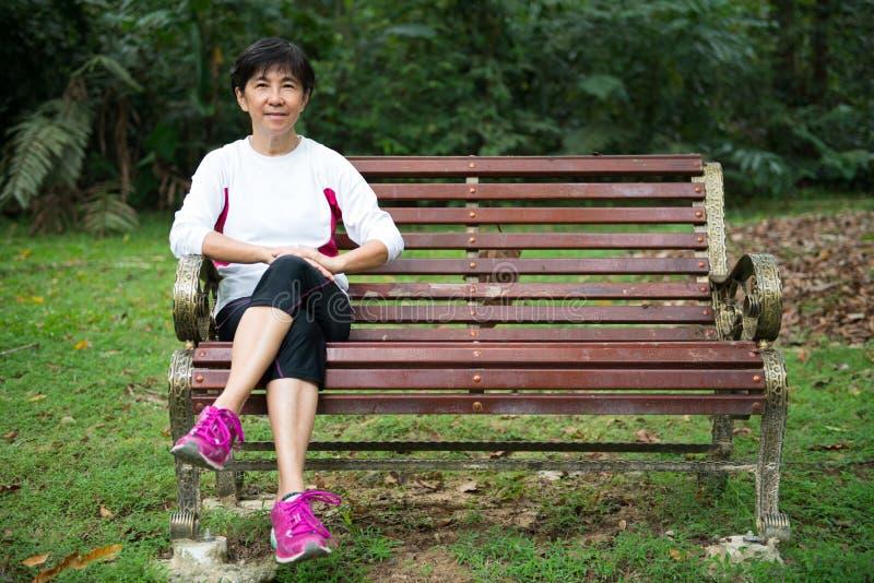 Mujer mayor que se relaja en banco de parque fotos de archivo