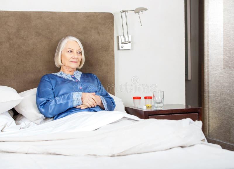 Mujer mayor que se relaja en cama imágenes de archivo libres de regalías