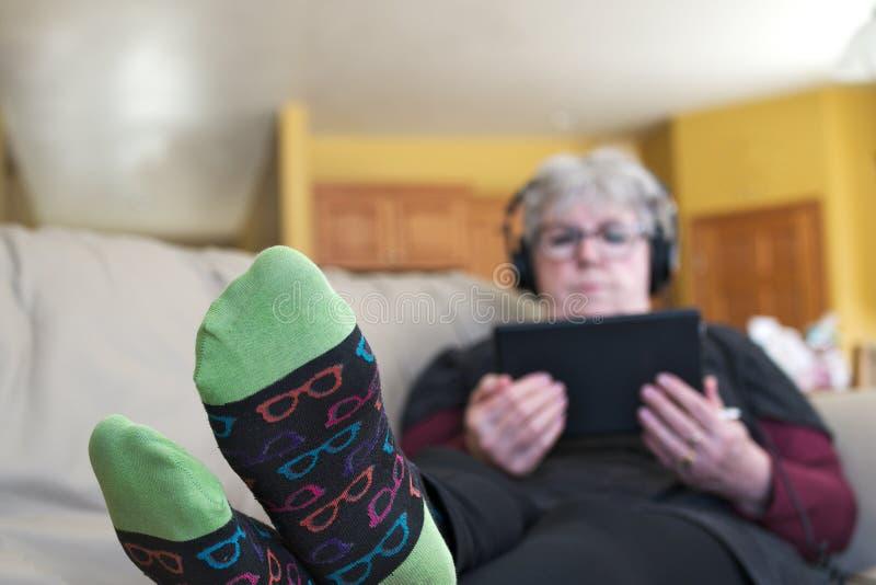 Mujer mayor que se relaja en el sof? en casa con la tableta y los auriculares imagenes de archivo