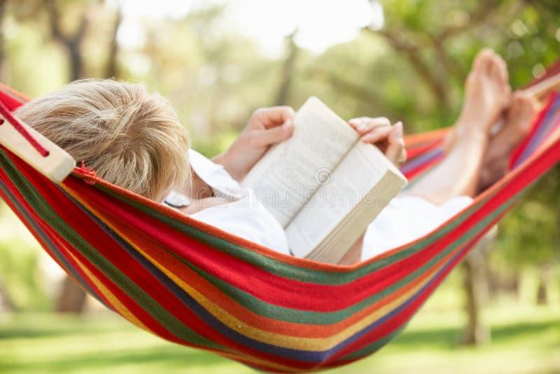 Mujer mayor que se relaja en hamaca con el libro imagen de archivo