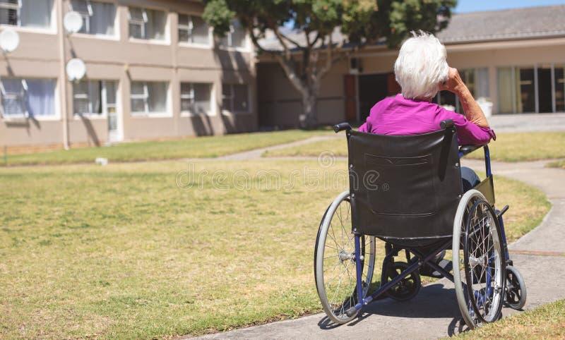 Mujer mayor que se relaja en la silla de ruedas en el parque de la cl?nica de reposo fotos de archivo