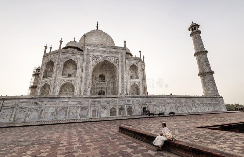 Mujer mayor que se sienta cerca de la piscina y que disfruta de la opinión de la puesta del sol Taj Mahal, Agra, la India foto de archivo