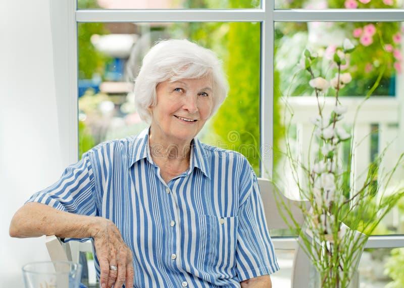 Mujer mayor que se sienta en casa imagen de archivo