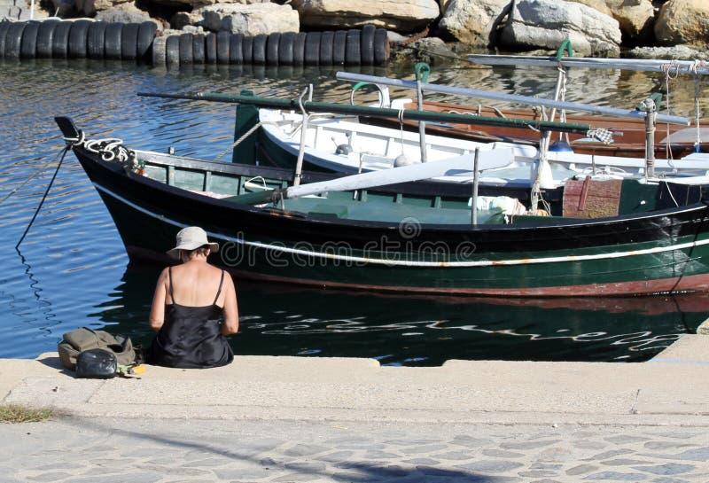 Mujer mayor que se sienta en el embarcadero Barcos en el fondo fotografía de archivo