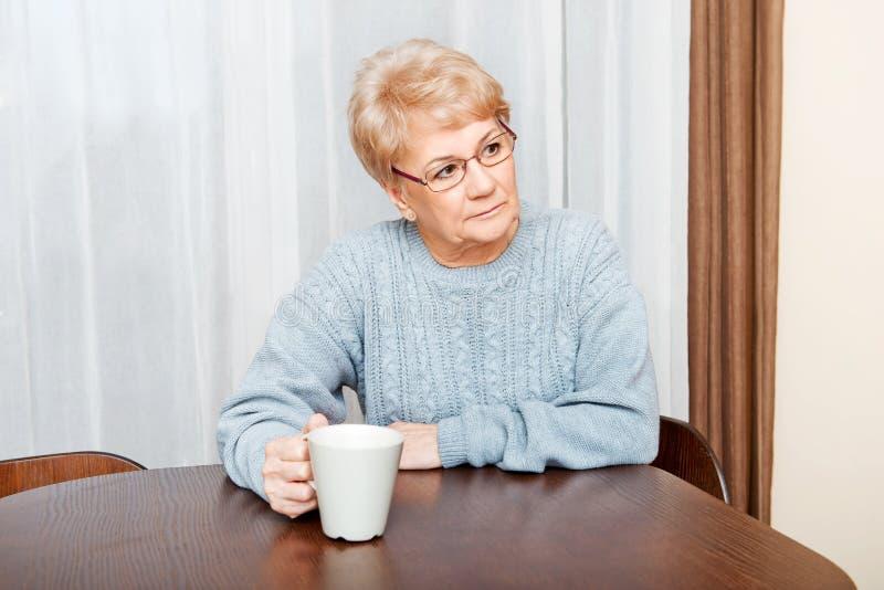 Mujer mayor que se sienta en el escritorio y el café o el té de consumición fotos de archivo