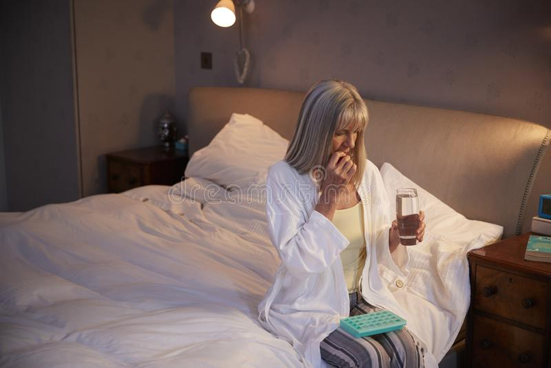 Mujer mayor que se sienta en la cama en casa que toma la medicación imagenes de archivo